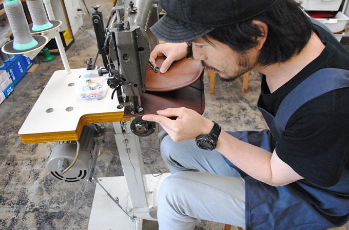 カブセのへり巻部の縫い作業。