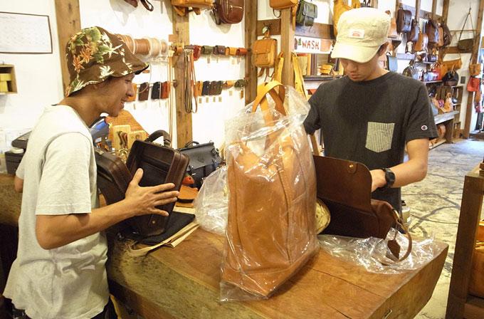 本店からお土産で持って行ったサンプルカバンを検品する仙台作り手:小田島(左)と庄子(右)。