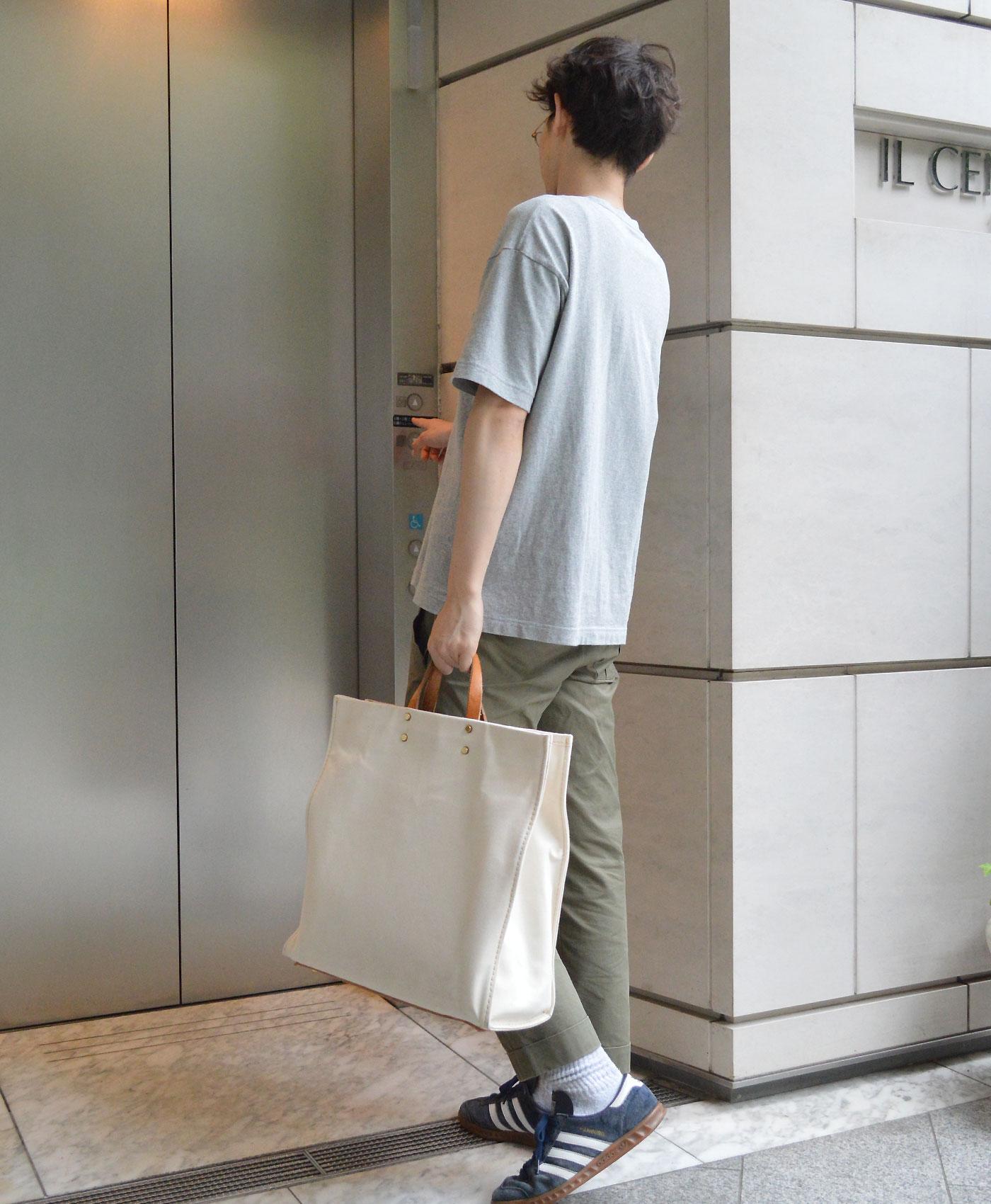 エレベーターに乗る西邑氏