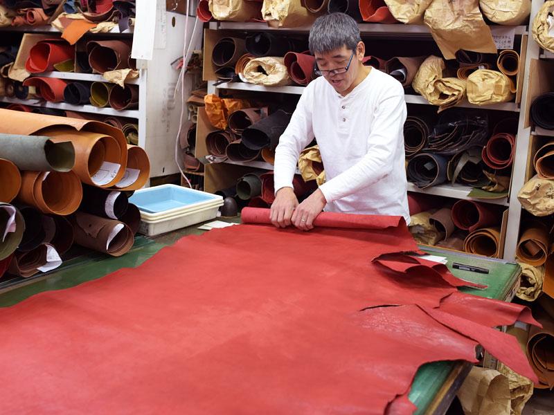 赤い革を巻く渋谷工房の作り手