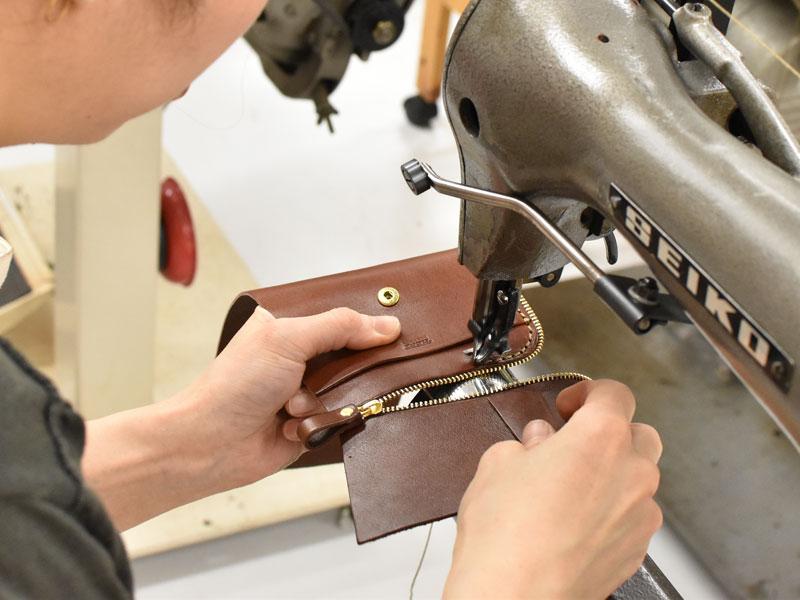 小型の二つ折り財布(WS-64)のファスナーを縫い付ける様子