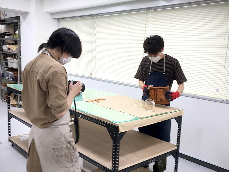 ヒコーキのりショルダー(WH-603)にウォッシュ加工の制作風景を撮影するスタッフ
