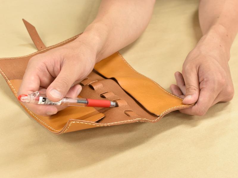 ロールペンケース(KP-100)のループにペンを収納する様子