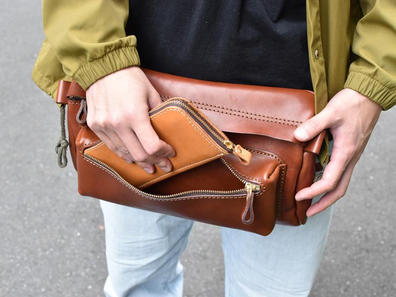 アクロバティック・ウエストバッグ(F-14)Lサイズの前ポケットから長財布を取り出す様子