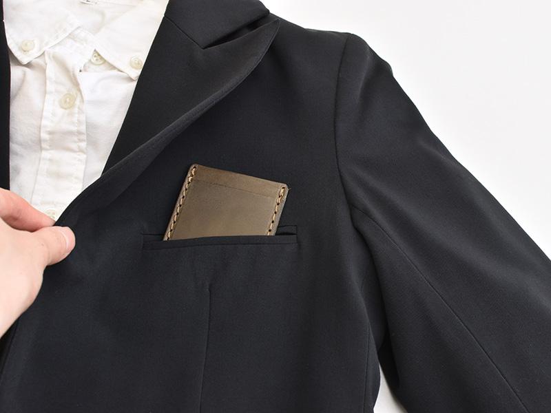 ネオミニマムパスケース(NSA-37)をジャケットの胸ポケットに収納する様子
