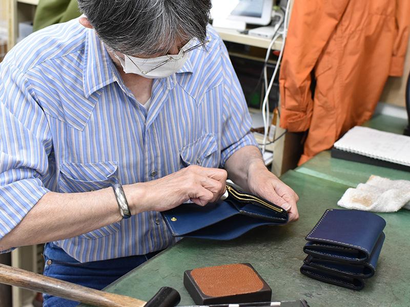 ネイビー革の小型の二つ折り財布(WS-64)を制作する様子