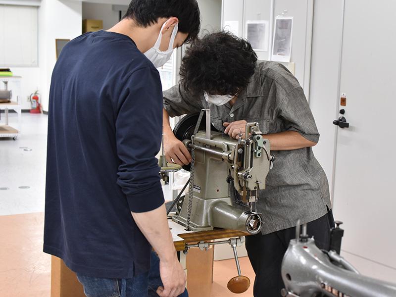 工房に届いたミシンを見る機材担当の作り手2