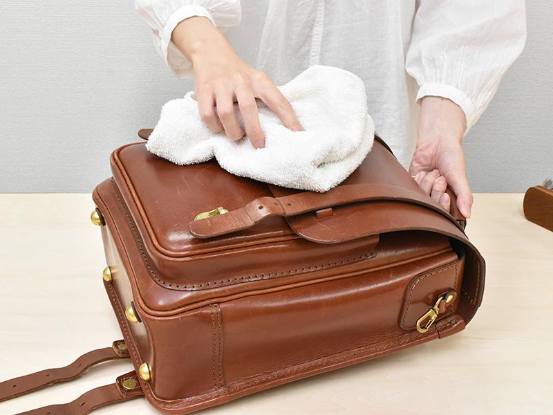 ランドセルを柔らかい布で乾拭きする様子