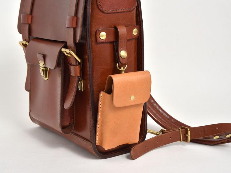 マルチスマホケース(KM-1)革色キャメルを鞄の側面に吊るした様子
