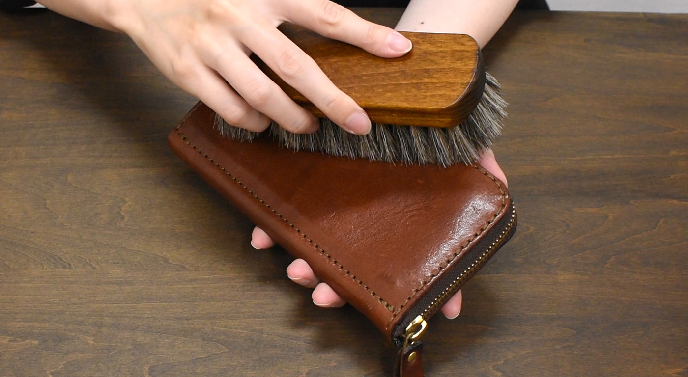 革財布をブラッシング(乾拭き)する様子