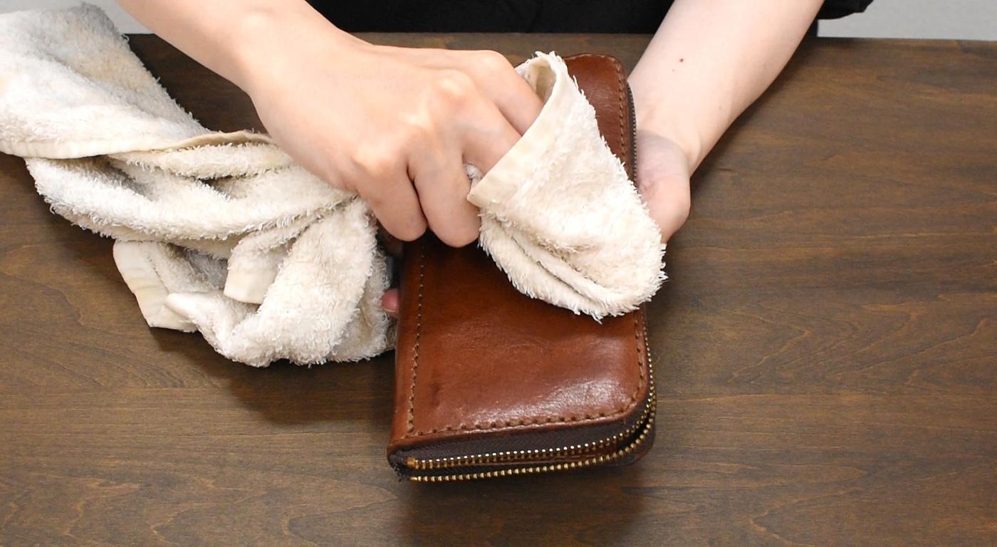 柔らかい布で革財布を水拭きする様子